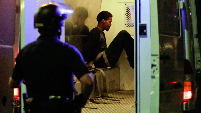 A Los Angeles police officer looks on as an arrested individual sits in the back of a van after a peaceful protest supporting Trayvon Martin turned unlawful in the Leimert Park neighborhood Los Angeles, California, July 15, 2013.(Reuters / Jason Redmond)