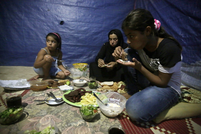 Fatima (C) a Syrian refugee widow, who lost her husband during the fighting in Homs, and her daughters have their Ramadan diner in their makeshift room in a neighbourhood of the Lebanese coastal city of Tripoli that hosts refugees on July 15, 2013 (AFP Photo / Joseph Eid)