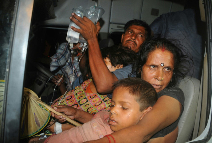 In this photograph taken on July 16, 2013 an Indian family, with their son who fell ill after consuming a free school meal, are transported outside the Patna Medical College Hospital in Patna. (AFP Photo)