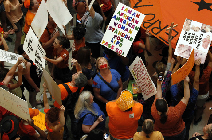Abortion rights (in orange) and anti-abortion advocates (in blue) rally in the rotunda of the State Capitol, as the state Senate meets to consider legislation restricting abortion rights in Austin, Texas July 12, 2013. (Reuters/Mike Stone)