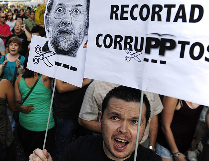 "People hold a poster reading ""Let's cut corrupted"" and a picture of Spanish Prime Minister Mariano Rajoy as they protest, on their way to the headquarters of the PP, blocked by the police, in Madrid on July 18, 2013. (AFP Photo / Dominique Faget)"