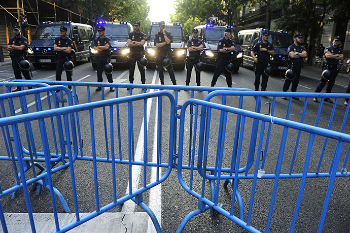 Policemen block the way to the PP (Popular Party)'s headquarters as people protest against Spanish Prime Minister Mariano Rajoy, in Madrid on July 18, 2013. (AFP Photo / Dominique Faget)