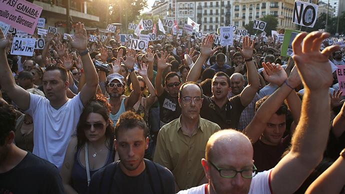 People raise their hands and shout slogans as they take part in a protest outside the People's Party (PP) headquarters in Madrid July 18, 2013. (Reuetrs / Juan Medina)