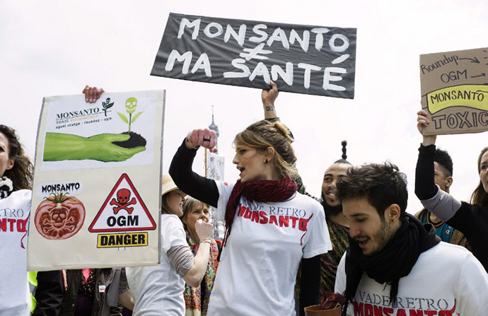 Anti-genetically modified organism activists gather on the Trocadero square near the Eiffel tower during a demonstration against GMOs and US chemical giant Monsanto on May 25, 2013 in Paris. (AFP Photo / Fred Dufour)