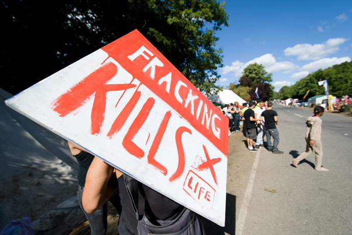 "A climate and anti-fracking protester holds a ""Fracking kills"" placard as he stands outside the test drill site operated by British energy firm Cuadrilla Resources in Balcombe, southern England, on August 20, 2013.(AFP Photo / Leon Neal)"