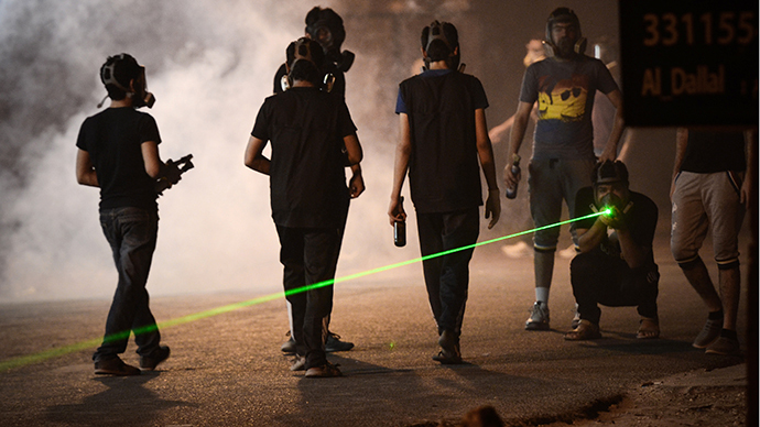 A Bahraini protestor flashes a laser during clashes with riot police following a protest to demand more rights and against the ruling regime in the village of Diraz, west of Manama, in the early hours of July 19, 2013. (AFP Photo / Mohammed Al-Shaikh)