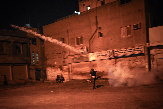 A Bahraini protestor throws back a tear gas canister fired by riot police during clashes following a protest to demand more rights and against the ruling regime in the village of Diraz, West of Manama, on July 19, 2013. (AFP Photo / Mohammed Al-Shaikh)