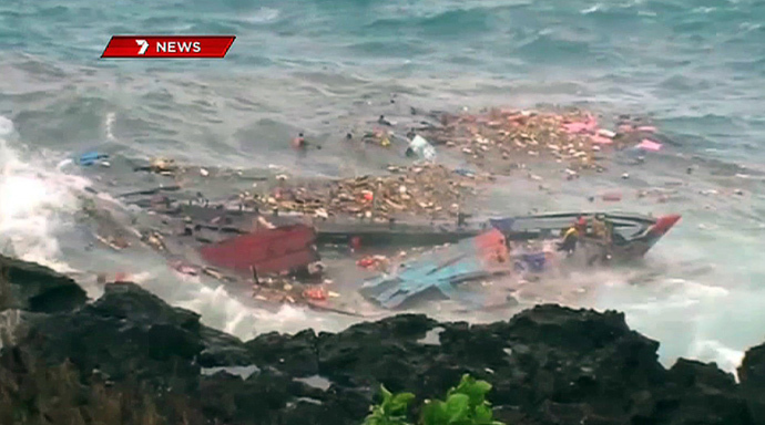 December 16, 2010 photo shows people floating amid and hanging onto the splintered remains of the wooden boat carrying refugees travelling from Asia after it smashed into the rocky coastline of Christmas Island (AFP Photo / Channel 7)