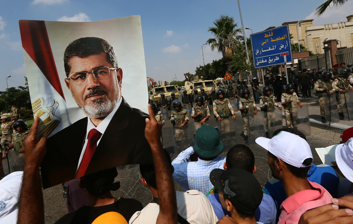 A supporter of the Muslim Brotherhood and ousted Egyptian president Mohamed Morsi raises a picture of the toppled leader in front of Army soldiers blocking Salah Salem highway in Cairo, on July 19, 2013 (AFP Photo / Marwan Naamani)