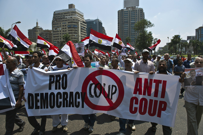 Supporters of the Muslim Brotherhood and toppled Egyptian president Mohamed Morsi hold a banner against his ouster as they march towards Cairo University to demand his reinstatement in Cairo on July 19, 2013 (AFP Photo / Khaled Desouki)