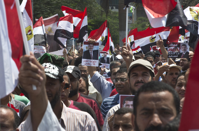Supporters of the Muslim Brotherhood and ousted Egyptian president Mohamed Morsi wave Egyptian flags while holding pictures of Morsi as they march towards Cairo University to demand his reinstatement in Cairo on July 19, 2013 (AFP Photo / Khaled Desouki)