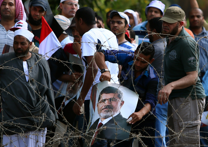 A supporter of the Muslim Brotherhood and ousted Egyptian president Mohamed Morsi hangs a picture of the toppled leader on the barbed wire in front of Army soldiers blocking Salah Salem highway in Cairo, on July 19, 2013 (AFP Photo / Marwan Naamani)