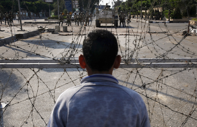 A supporter of deposed Egyptian President Mohamed Mursi shouts slogans in front of barbed wire and army soldiers at the Republican Guard headquarters in Nasr City, a suburb of Cairo July 19, 2013 (Reuters / Amr Abdallah Dalsh)