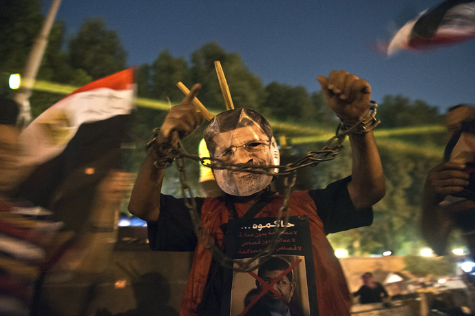 An man wearing a mask of ousted president Mohamed Morsi shows his handcuffed hands outside the presidential palace in Cairo on July 19, 2013 (AFP Photo / Khaled Desouki)