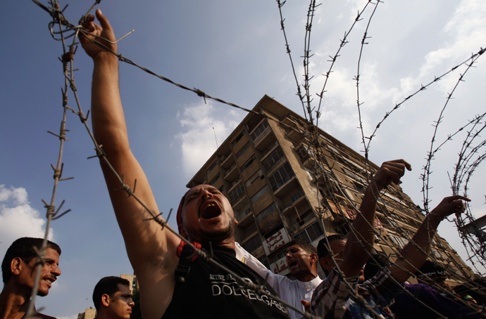 Members of the Muslim Brotherhood and supporters of deposed Egyptian President Mohamed Mursi shout slogans behind barbed wire outside the Republican Guard headquarters in Cairo July 19, 2013 (Reuters / Amr Abdallah Dalsh)