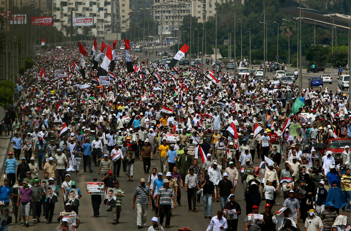 Supporters of the Muslim Brotherhood and ousted Egyptian president Mohamed Morsi raise pictures of the toppled leader and wave the national flag during a demonstration in Cairo, on July 19, 2013 (AFP Photo / Marwan Naamani)