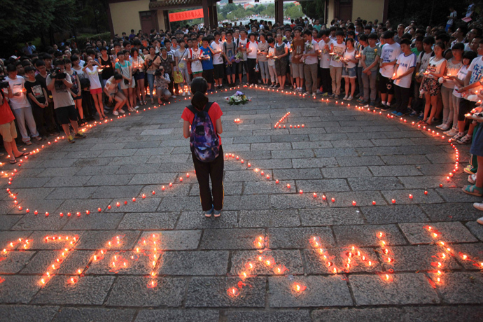Students of the Jiangshan Middle School light candles to form a heart shape and initials (below), of the victims Yang Mengyuan and Wang Linjia of the Asiana Airlines crash, in Quzhou, Zhejiang province July 8, 2013 (Reuters / Stringer)