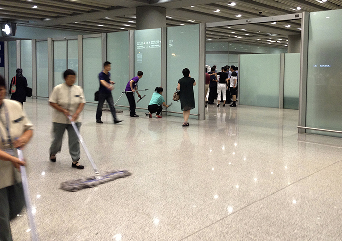 Airport staffs clean the floor and glasses at the arrival gate B where an explosion occurred at the Terminal 3 of Beijing Capital International Airport in Beijing, July 20, 2013. (Reuters / Jason Lee)