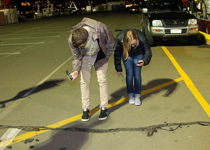 Students photograph a crack on the ground on the wharf on the waterfront after a 6.5 magnitude earthquake hit Wellington on July 21, 2013.(AFP Photo / Marty Melville)