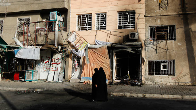 Women walk past the site of a car bomb attack at the neighbourhood of Tobchi in Baghdad, July 21, 2013. (Reuters / Thaier al-Sudani)