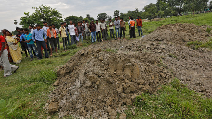 Villagers stand next to mass graves of the school children who died after consuming contaminated meals given to them at a school on Tuesday, at Chapra district in the eastern Indian state of Bihar July 18, 2013.(Reuters / Adnan Abidi)