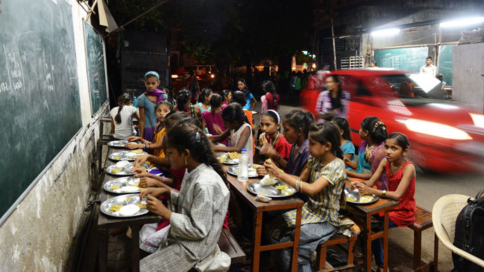 Indian students eat a meal at the Footpath School in Ahmedabad on late July 20, 2013.(AFP Photo / Sam Panthaky)
