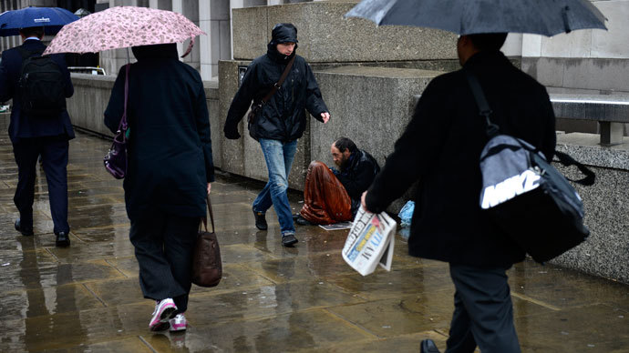 A homeless man sits in the rain as commuters make their way to work across London Bridge in London.(Reuters / Dylan Martinez)
