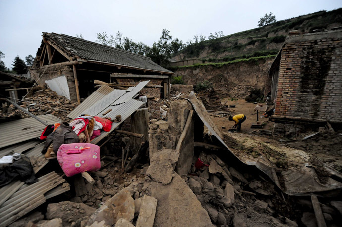 A woman (R) works beside damaged houses in Meichuan township in Dingxi, in northwest China's Gansu province, on July 23, 2013. (AFP Photo)