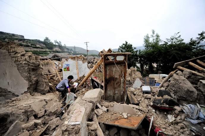 A woman (L) works beside damaged houses in Meichuan township in Dingxi, in northwest China's Gansu province, on July 23, 2013. (AFP Photo)