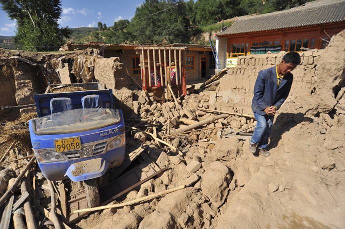 A man walks past a collapsed house after a 6.6 magnitude earthquake in Minxian county, Dingxi, Gansu province, July 22, 2013. (Reuters)