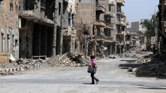 A Syrian girl crosses the street holding a bag in the centre of Syria's northeastern city of Deir Ezzor.(AFP Photo / Abo Shuja)