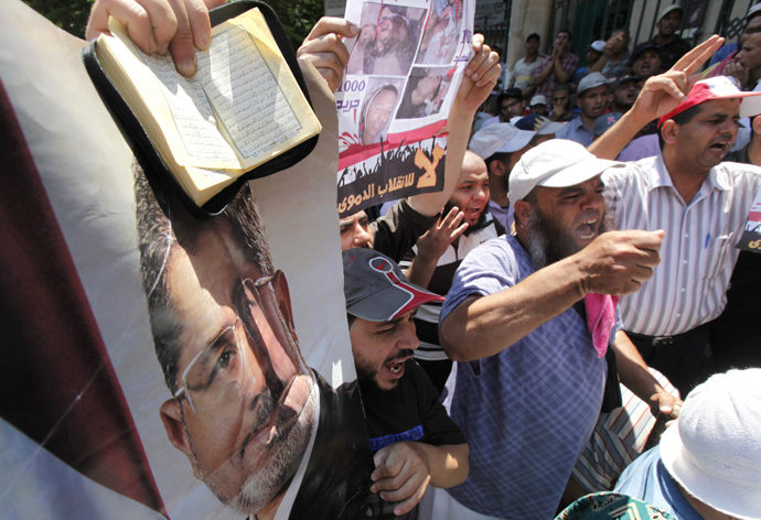 Members of the Muslim Brotherhood and supporters of deposed Egyptian President Mohamed Mursi shout slogans while holding posters of Mursi and copies of the Koran during a protest in Cairo July 22, 2013 (Reuters / Mohamed Abd El Ghany)