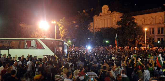 Protestors face Bulgarian riot policemen making way for lawmakers and parliament staff driven in a bus during an anti-government protest in Sofia on July 23, 2013. (AFP Photo/Dimitar Dilkoff)