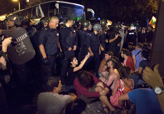 Protesters opposing the Socialist-led government try to stop a heavily guarded bus trying to get deputies out of the parliament where they had been discussing budget measures, in Sofia July 23, 2013. (Reuters)