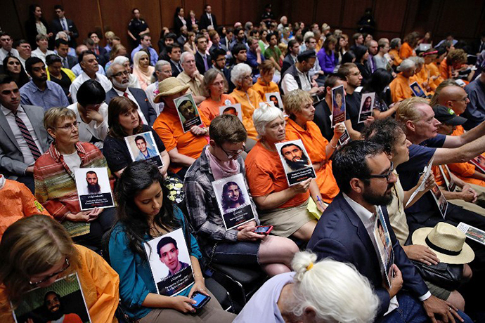 Supporters of closing the Guantanamo Bay Naval Base detention facility hold pictures of prisoners being held at the facility while viewing a hearing of the Senate Judiciary Committee July 24, 2013 in Washington, DC. (AFP Photo / Win Mcnamee)