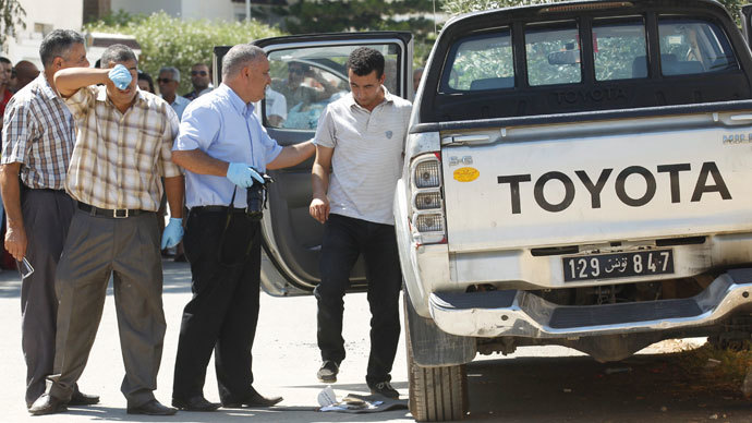 Forensic inspectors examine the car of Tunisian opposition politician Mohamed Brahmi, who was shot dead outside his home, in Tunis July 25, 2013.(Reuters / Zoubeir Souissi)