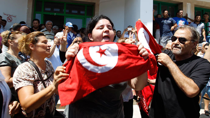 Assassinated Tunisian opposition politician Mohamed Brahmi's daughter Balkis (C) holds a Tunisian flag as she mourns his death in Tunis July 25, 2013. (Reuters / Zoubeir Souissi)