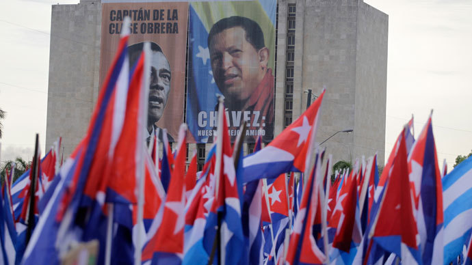 People carry flags near a poster of late Venezuelan leader Hugo Chavez during the Mayday parade in Havana's Revolution Square May 1, 2013.(Reuters / Desmond Boylan)