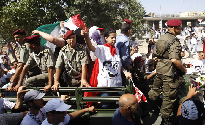 The daughter (C) of slain Tunisian opposition politician Mohamed Brahmi gestures during his funeral procession towards the nearby cemetery of El-Jellaz, where he is to be buried, in Tunis July 27, 2013. (Reuters/Zoubeir Souissi)