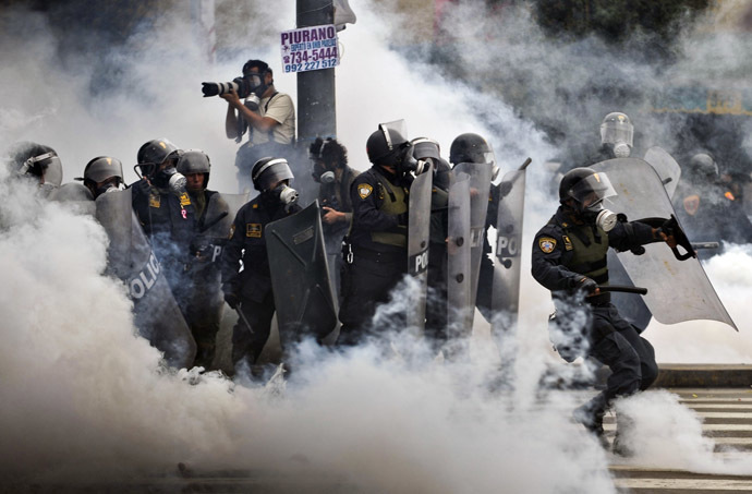 Riot policemen stand in a tear gas cloud during clashes within a student and workers protest against the government, in Lima on July 27, 2013. (AFP Photo/Ernesto Benavides)