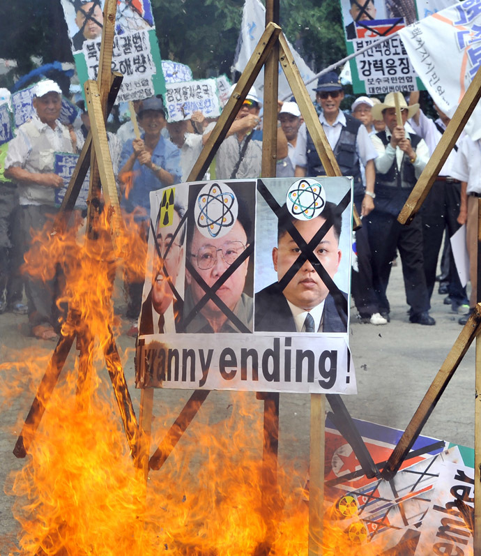 South Korean conservative activists burn portraits of North Korea's founder Kim Il-Sung (R), late leader Kim Jong-Il (C) and present leader Kim Jong-Un during an anti-North Korea rally at a park in Seoul on July 27, 2013 to mark the 60th anniversary of ceasefire agreement and UN forces' participation in the Korean War. (AFP Photo/Jung Yeon-Je)
