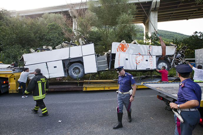 Workers remove the wreck of a bus on July 29, 2013 near Baiano, following a crash the day before on the road between Monteforte Irpino and Baiano, southern Italy. (AFP Photo / Carlo Hermann)