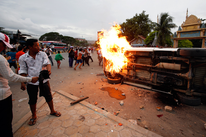People set a police car on fire during a clash at the end of election day in Phnom Penh July 28, 2013 (Reuters / Samrang Pring)
