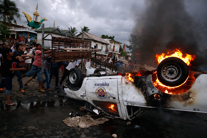 Protesters throw a bench onto a burning police vehicle following a brief clash at the end of election day in Phnom Penh July 28, 2013 (Reuters / Damir Sagolj)