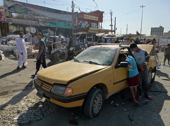 Iraqis inspect the site of a car bomb explosion in the impoverished district of Sadr City in Baghdad on July 29, 2013, after 11 car bombs hit nine different areas of Baghdad, seven of them Shiite-majority, while another exploded in Mahmudiyah to the south of the capital. (AFP Photo / Ahmad Al-Rubaye)