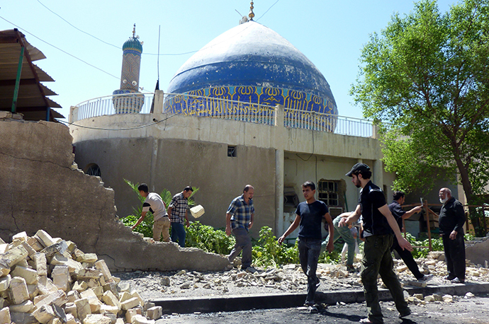Iraqis remove the stones of a wall that was destroyed in a car bombing outside Ahl al-Bayya' mosque on July 29, 2013 in south eastern Baghdad. (AFP Photo / Ali Al-Saadi)
