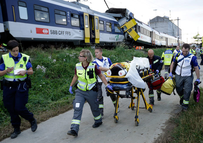 Swiss rescue workers wheel a wounded person on a stretcher after two regional trains crashed head on near Granges-Pres-Marnand near Payerne in western Switzerland July 29, 2013.(Reuters / Denis Balibouse)