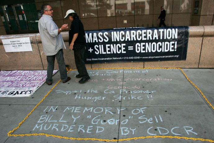 "Keith James (R) and ""Dee"" stand near signage during a rally supporting hunger strikers in the California prison system in Los Angeles, California July 29, 2013. (Reuters / Jonathan Alcorn)"