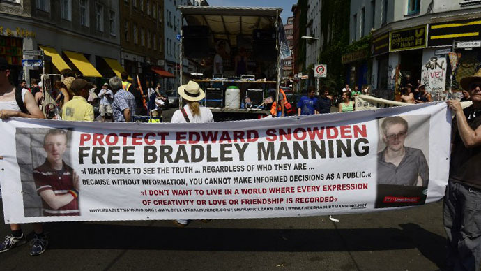 Demonstrators hold a banner in support of former US agent of the National Security Agency, Edward Snowden and U.S. Army Private First Class Bradley Manning as they take part in a protest against the US National Security Agency (NSA) collecting German emails, online chats and phone calls and sharing some of it with the country's intelligence services in Berlin on July 27, 2013. (AFP Photo / John Macdougall)