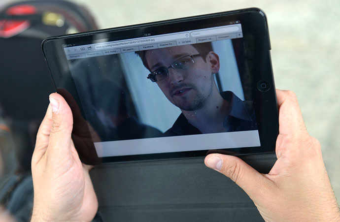 A journalist studies a photo of former CIA employee Edward Snowden, at Sheremetyevo Airport (RIA Novosti / Valeriy Melnikov)
